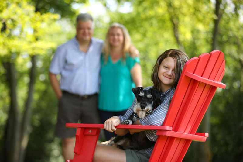 Sophia Pseno, 13, is photographed with her dog, Eggsy, and her parents, Steve and Carol, outside their Inverness home on Aug. 5, 2020. To help with Sophia's learning over the summer, the family has been reading and baking together. (Stacey Wescott / Chicago Tribune)